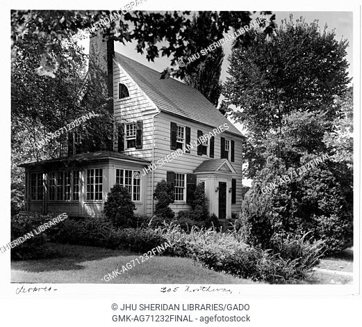 Landscape diagonal shot of a white house with an annexed sun room, surrounded by many trees and shrubs with leaves, Roland Park/Guilford, Baltimore, Maryland