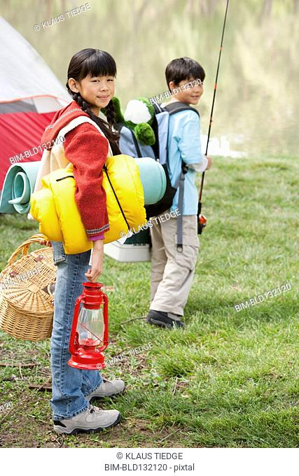 Children carrying camping gear outdoors