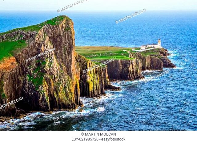 View of Neist Point lighthouse and rocky ocean coastline, Scotland