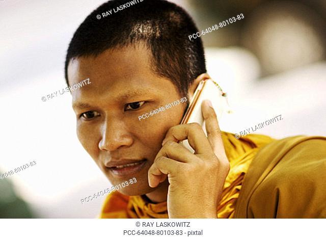 Thailand, Bangkok, Buddhist monk talking on cellphone