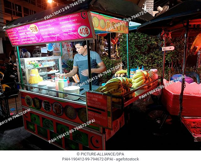 """25 February 2019, Thailand, Karon Beach: A booth offering the traditional Thai dessert """"""""Roti"""""""" at temple market in Karon Beach"""