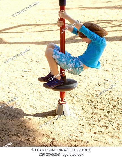 Boy with Blond Hair Spinning on a Pole at Playground