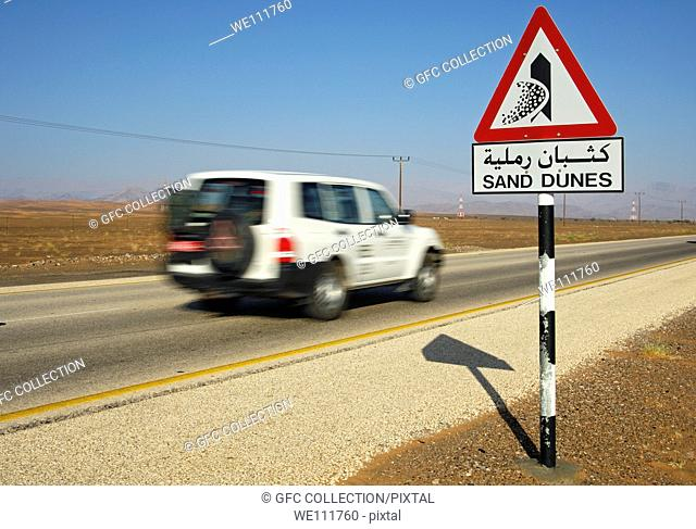 Road sign warning in English and Arabic of shifting sand dunes at a desert road, Sultanate of Oman