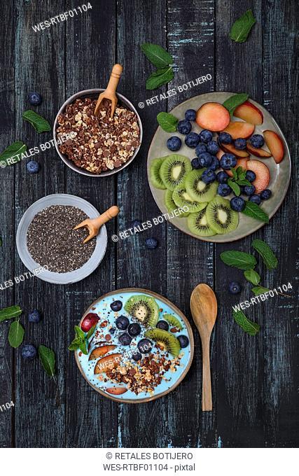 Superfood smoothie bowl with chia seeds, blueberries, nectarine, kiwi and chocolate granola