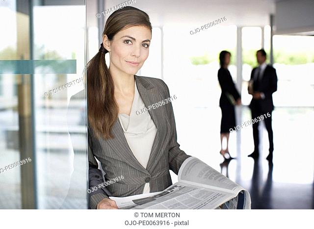 Businesswoman reading newspaper in lobby