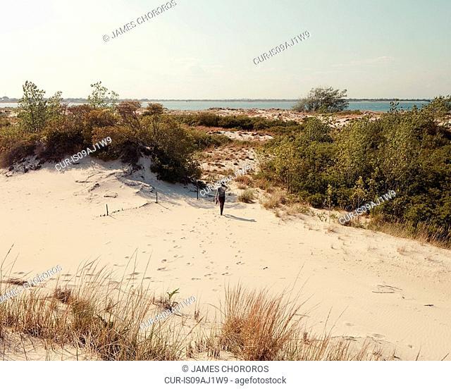 Mid adult woman walking over sand dunes, Jones beach, New York State, USA