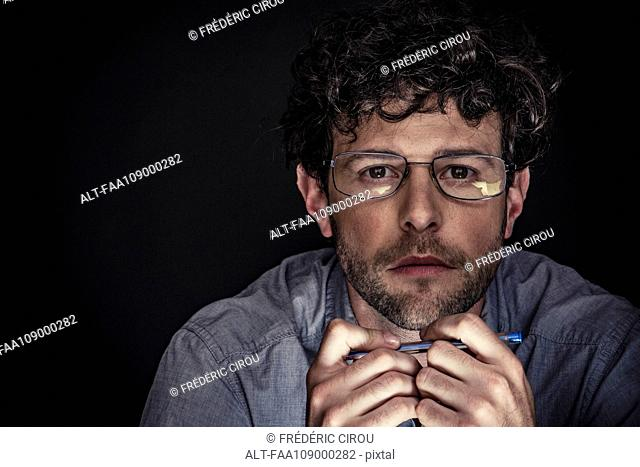 Man wearing glasses and holding pen, portrait