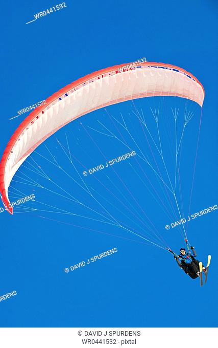 A Paraglider pilot connected to her wing by the lines