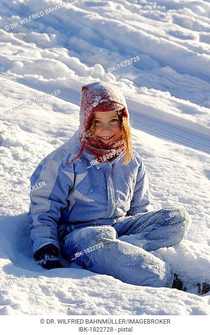 Child sitting in snow, powder snow