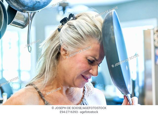 A 52 year old blond woman banging her head against a frying pan