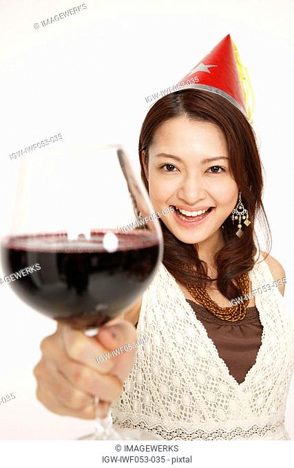 Young woman holding wineglass, smiling, portrait