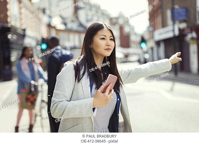 Young businesswoman with cell phone hailing taxi on sunny urban street