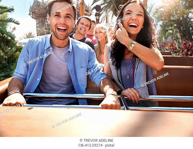 Enthusiastic young couple riding amusement park ride