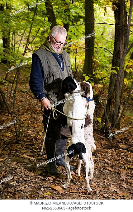 Elderly man caresses his dogs while looking for truffles in the woods one of the dogs looks into his pocket