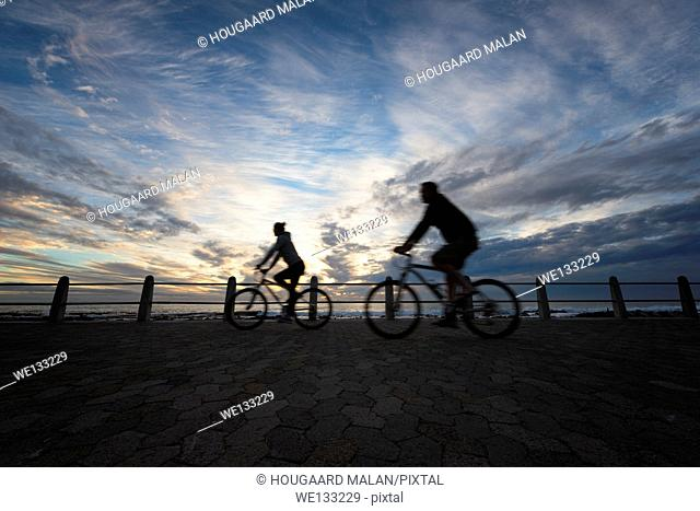 Wide angle photo of people cyclingalong a seaside promenade. Mouille Point, Cape Town, South Africa