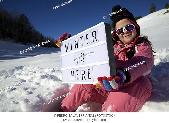 """Slogan """"""""winter is here"""""""" held by a girl in a snowy landscape"""