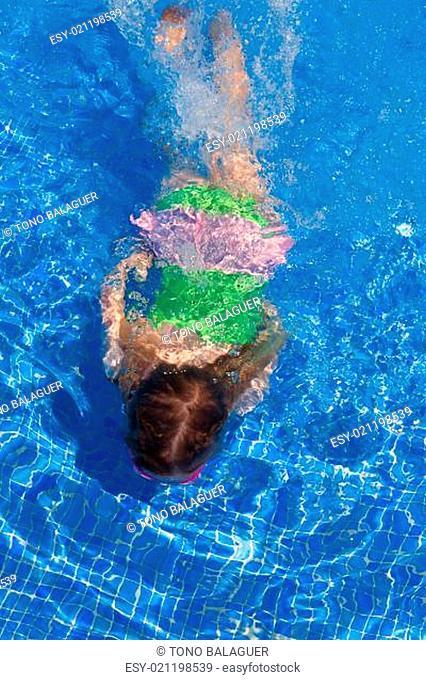children gilr swimming underwater in blue pool