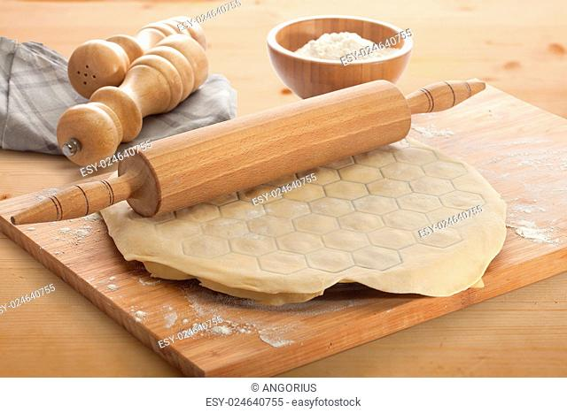 Dough on the form for making dumplings on the wooden board