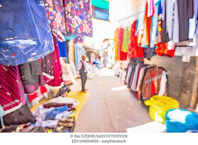 View of a bazaar with lots traditional clothes on foreground for sale in Mardin,Turkey