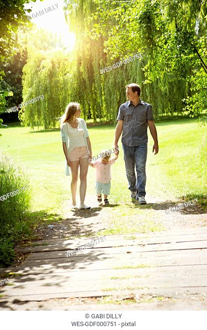 Parents walking with their little son in a park