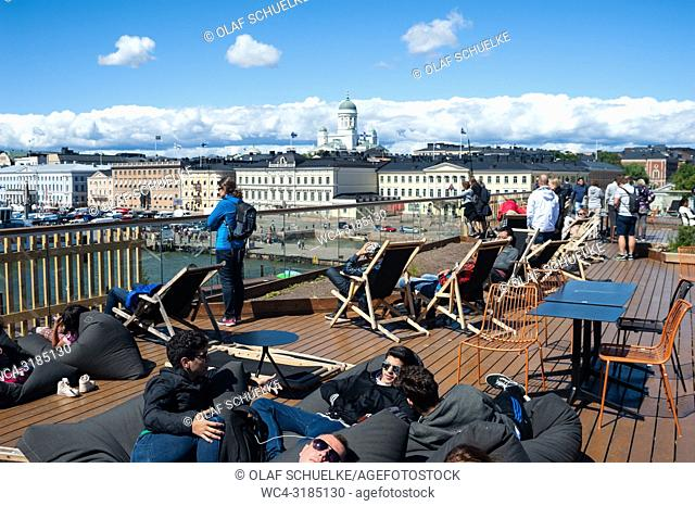 Helsinki, Finland, Europe - People sunbathe on the rooftop of the Allas Sea Pool with the central market square, the Presidential Palace and the Helsinki...