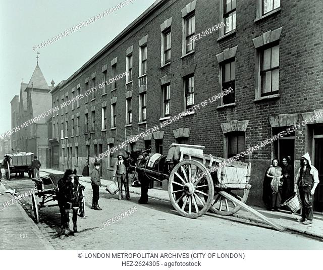 Dustmen and dust cart in Beckett Street, Camberwell, London, 1903. A horse waits with a cart while men with baskets collect refuse from three-storey terraced...