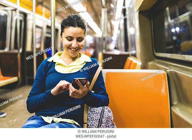 USA, New York, woman using cell phone in subway