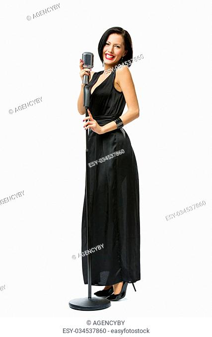 Full-length portrait of woman singer wearing long black evening dress and holding microphone