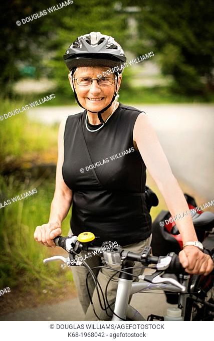 A woman, 66, with her bicycle on Saturna Island, Gulf Islands, British Columbia, Canada
