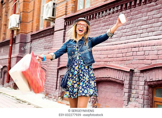 Happy tourist girl with bags and coffee cup walking on city street