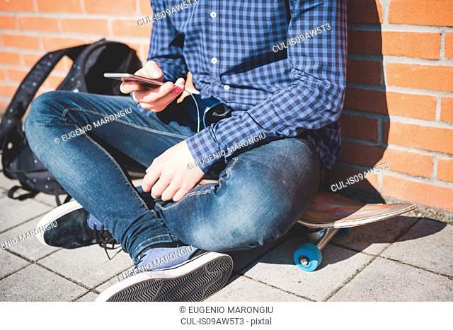 Neck down view of young male urban skateboarder sitting on sidewalk reading smartphone text