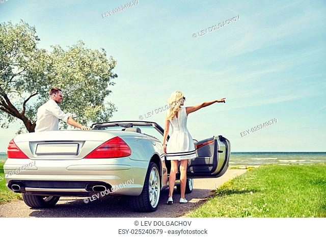 transport, travel, road trip and people concept - happy man and woman near cabriolet car at sea side