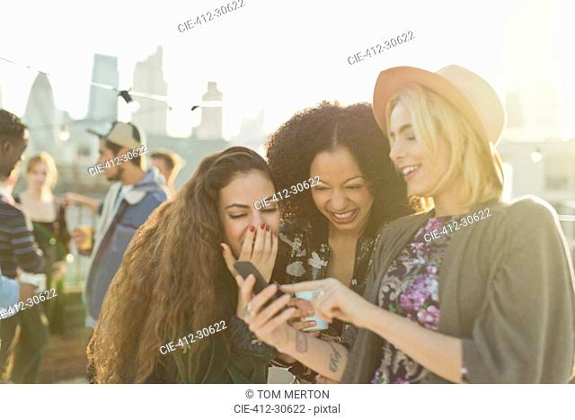 Young women laughing and texting with cell phone at rooftop party