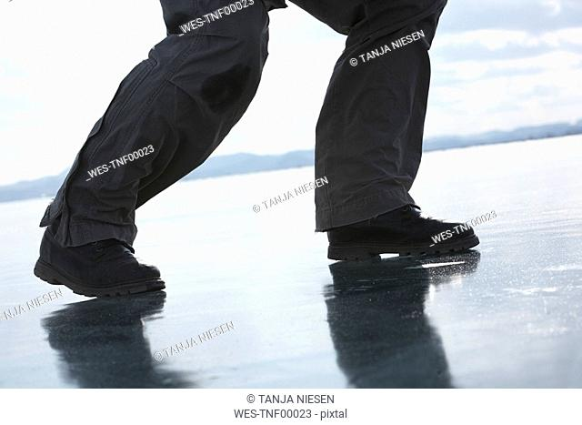 Russia.Lake Baikal, person on frozen lake, low section, close-up