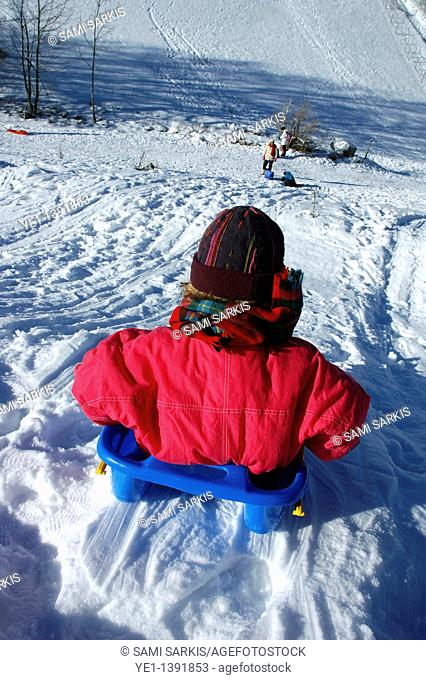 Young girl sledding down a snowy hill