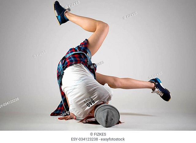 One fit young woman wearing casual plaid shirt performing breakdance moves on the floor. Modern style beautiful teen dancer working out, dancing