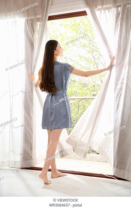The young woman drew out the curtain and looked out