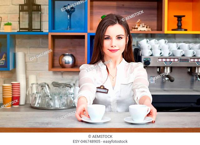 beautiful young girl preparing coffee in a cafe barista