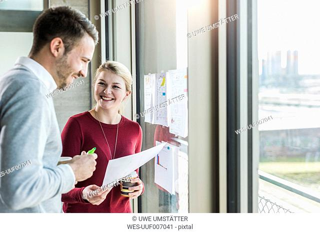 Two smiling colleagues with papers at office window