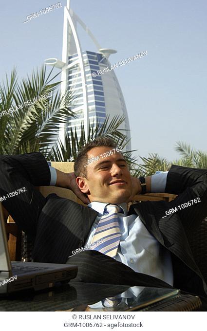 Relaxed businessman in Dubai (with Burj Al Arab hotel in background)