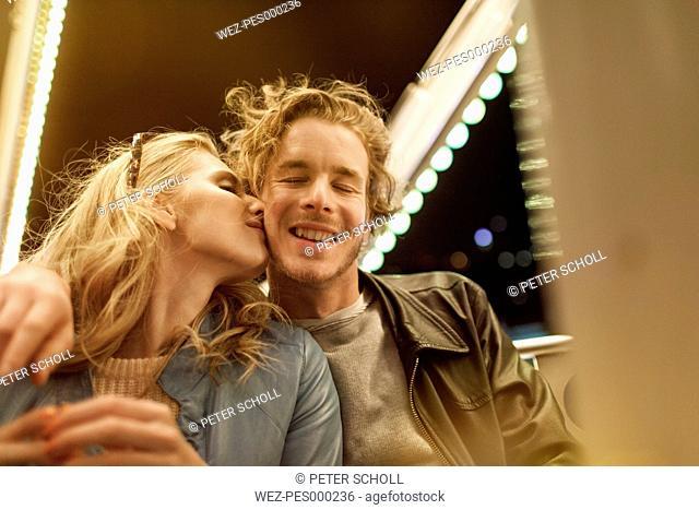 Young couple at fun fair kissing
