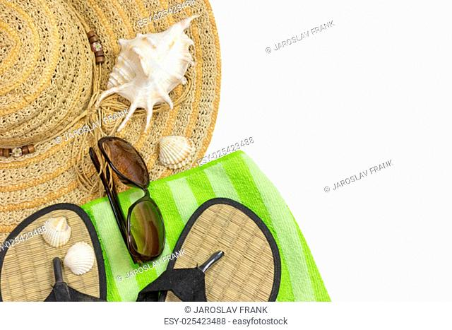 Straw hat, sunglasses, beach sandals, green towel and seashells are on the left side of the photo isolated on the white background