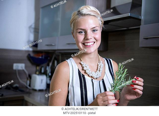 Portrait of a young woman holding rosemary in the kitchen and smiling, Bavaria, Germany