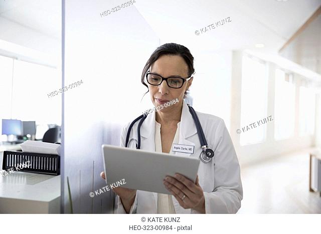 Female doctor using digital tablet in clinic corridor