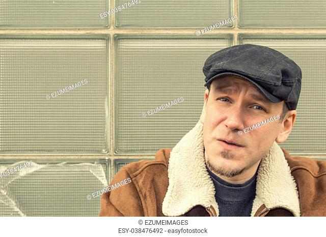 cd66c1d0 Cool guy in aviator jacket and newsie cap relaxes against a glass wall