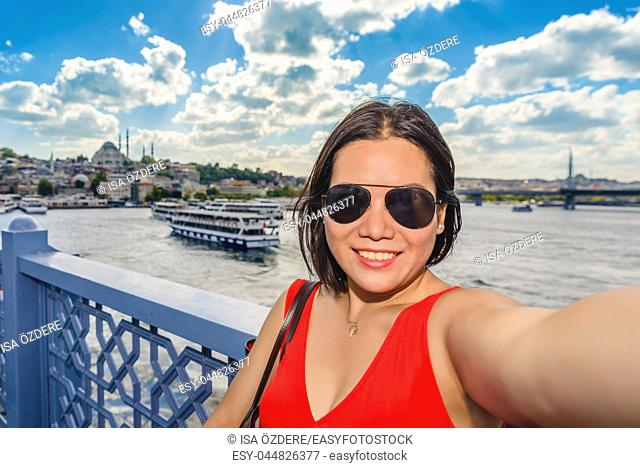 Beautiful Chinese woman takes selfie with view of Suleymaniye Mosque and Bosphorus in Istanbul,Turkey