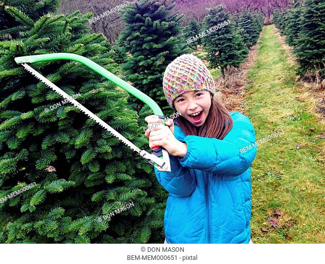 Mixed race girl holding saw in Christmas tree patch
