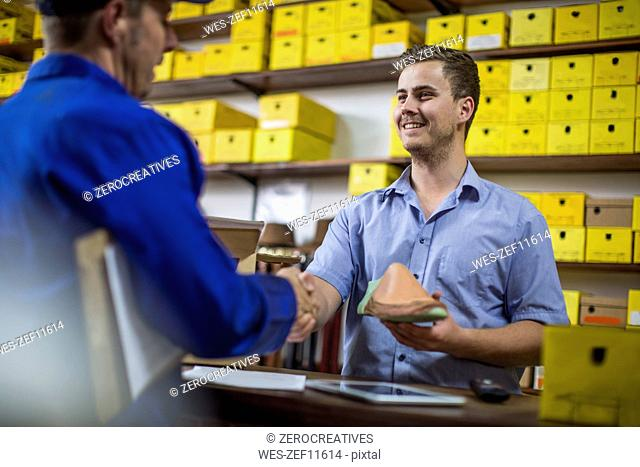 Man in warehouse shaking hands with delivery man