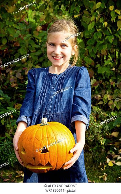 Girl holding Jack O'Lantern, portrait