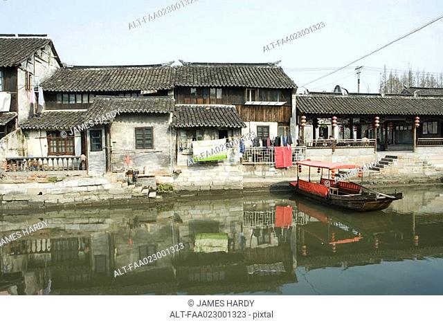China, Guangdong Province, houses on edge of water, with boat
